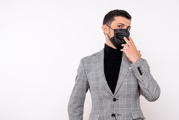 白い孤立した背景に立っているマスクを身に着けているスーツのハンサムな男の正面図