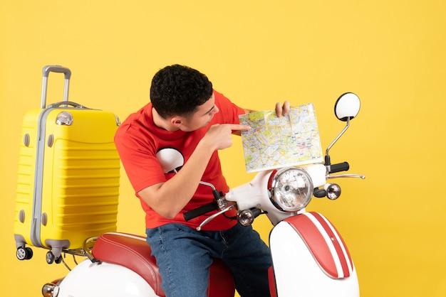 Vista frontale uomo bello sul ciclomotore guardando la mappa