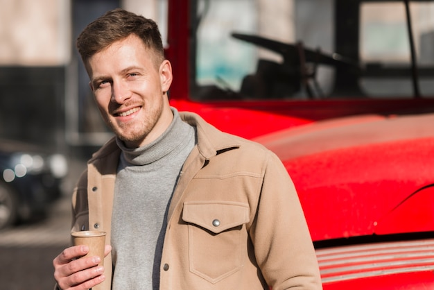 Front view of handsome man posing while holding coffee cup