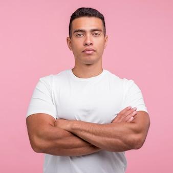 Vista frontale dell'uomo bello in posa con le braccia incrociate