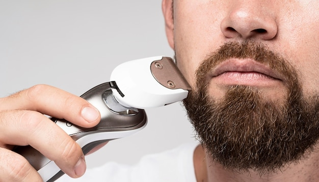 Front view handsome man shaving close-up