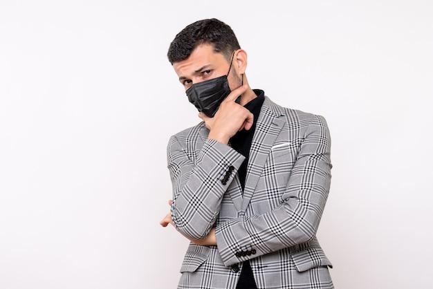 Vista frontale bell'uomo in tuta mettendo la mano sul mento in piedi su sfondo bianco isolato