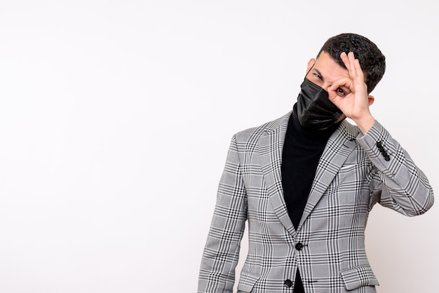 Front view handsome man in suit putting okey sign in front of his eye standing on white isolated background