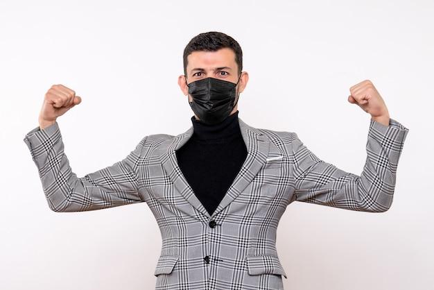 Vista frontale bell'uomo in tuta che mostra i muscoli in piedi su sfondo bianco isolato