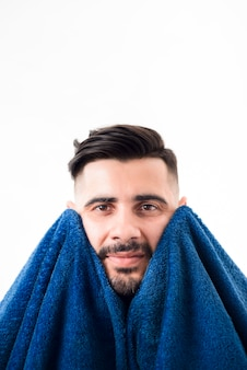 Front view handsome man wiping himself with a blue towel