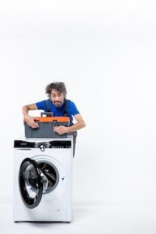 Vista frontale bel riparatore che chiude la borsa degli attrezzi dietro la lavatrice su uno spazio bianco