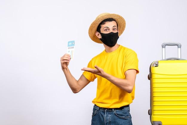 Вид спереди красивый турист в желтой футболке, стоящий возле желтого чемодана с проездным билетом