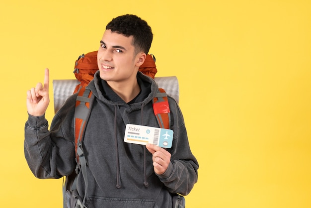 Front view handsome traveller man with backpack holding ticket pointing at ceiling