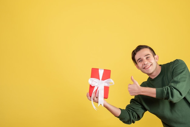 Front view handsome young man holding gift making thumb up sign on yellow
