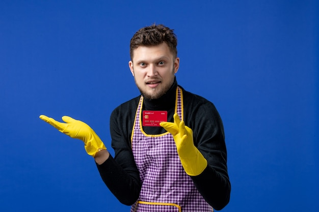 파란색 공간에 카드를 들고 검은 스웨터에 전면 보기 잘생긴 젊은 남자