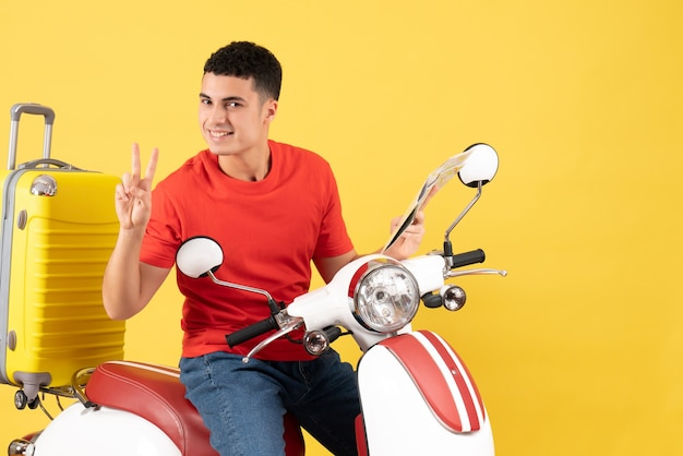 Front view handsome young man on moped holding map making victory sign
