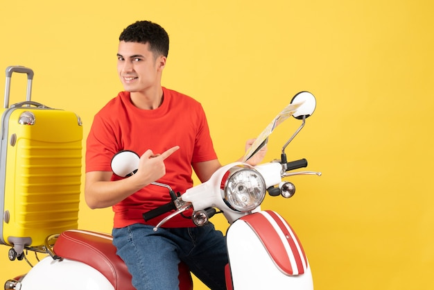 Vista frontale bel giovane uomo sulla mappa della holding del ciclomotore