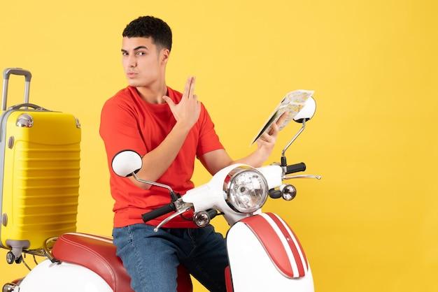 Vista frontale bel giovane sul ciclomotore che fa la mappa della holding della pistola dito