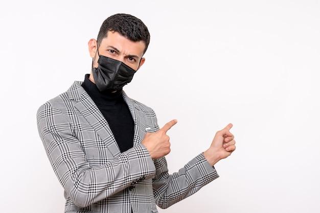 Vista frontale bel giovane con maschera nera che punta a dietro in piedi su sfondo bianco isolato