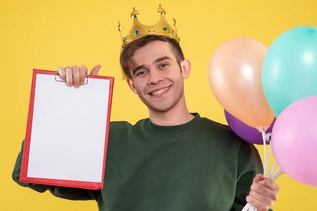 Vista frontale bel giovane con corona che tiene palloncini e appunti su giallo