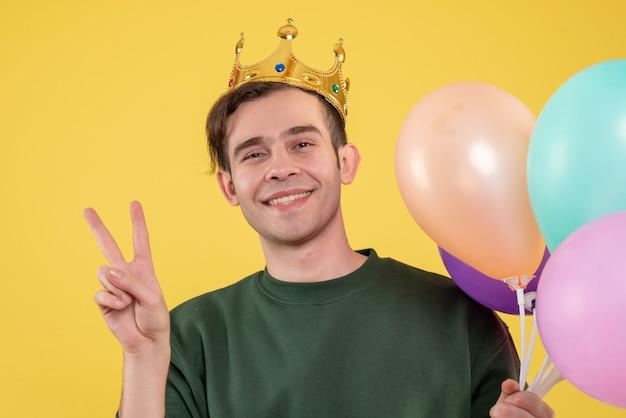Vista frontale bel giovane con corona che tiene palloncini facendo segno di vittoria su giallo