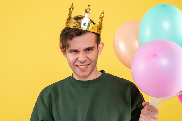 Vista frontale bel giovane con corona che tiene palloncini su giallo