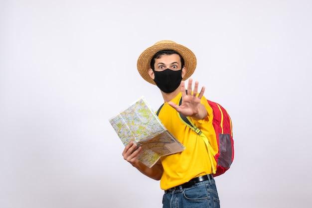 Вид спереди красивый молодой человек с красным рюкзаком и маской, держащий карту