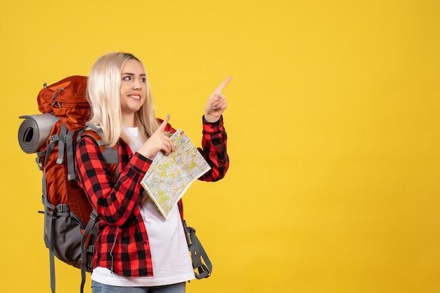 Вид спереди счастливая блондинка со своим рюкзаком, держащая карту, стоящую на желтой стене