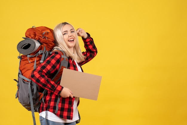 Front view happy blonde woman with her backpack holding up cardboard