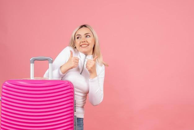 Вид спереди счастливая блондинка с розовым чемоданом показывает палец вверх