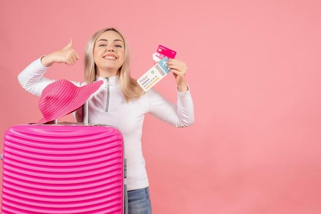 Вид спереди счастливая блондинка с розовым чемоданом, держащая карту и билет на самолет, показывает палец вверх