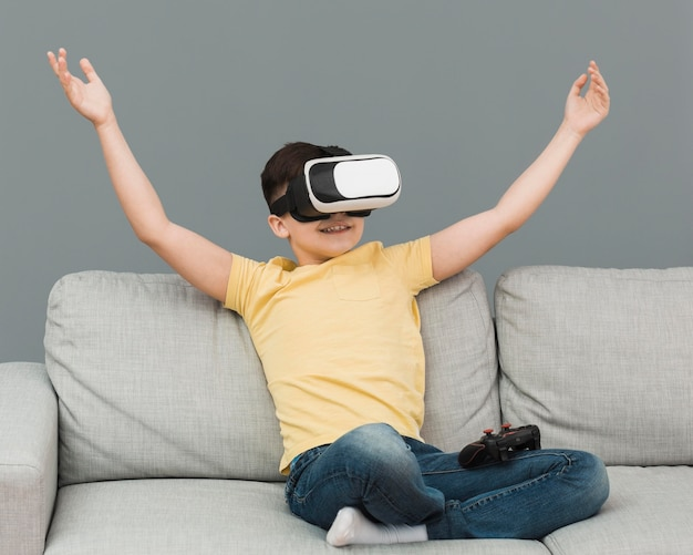 Front view of happy boy using virtual reality headset