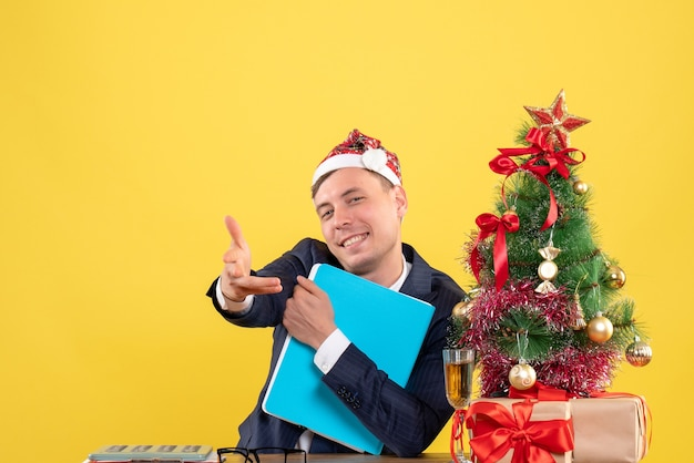 Front view of happy business man giving hand sitting at the table near xmas tree and presents on yellow
