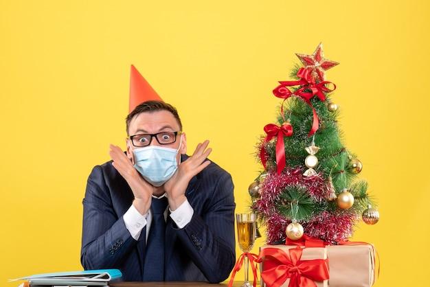 Vista frontale dell'uomo felice di affari che si siede al tavolo vicino all'albero di natale e regali su giallo