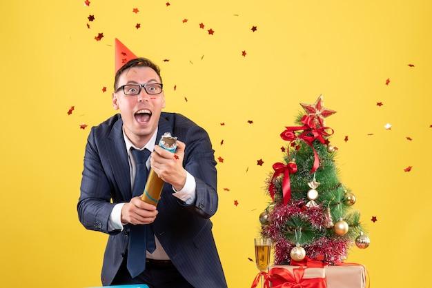 Vista frontale dell'uomo felice di affari che utilizza il popper del partito che sta dietro il tavolo vicino all'albero di natale e ai regali su colore giallo