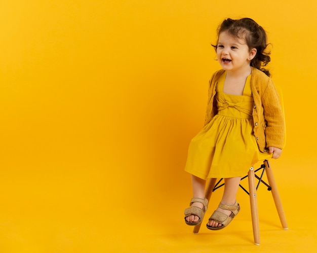 Front view of happy child posing while sitting on chair