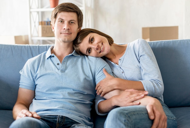 Front view of happy couple on couch while packing to move
