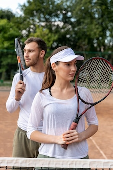 Front view happy couple on tennis court