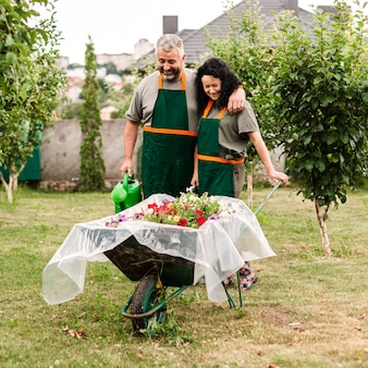 Front view happy couple with wheelbarrow