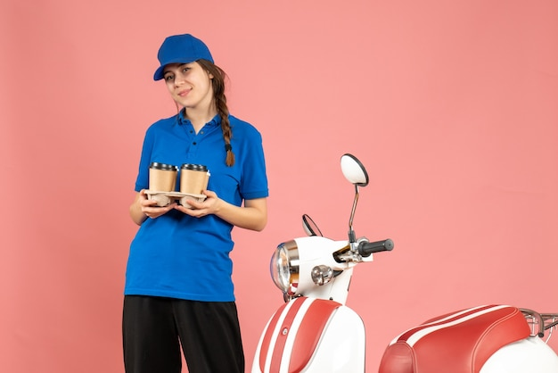 Front view of happy courier girl standing next to motorcycle holding coffee on pastel peach color background
