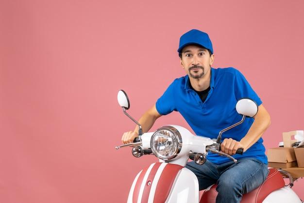 Vista frontale del corriere felice che indossa un cappello seduto su uno scooter su sfondo color pesca pastello pastel