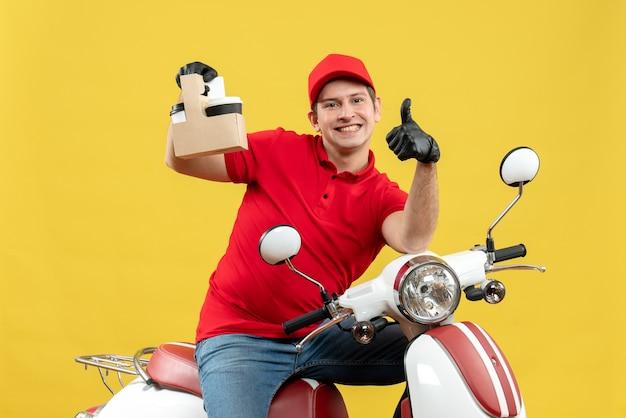 Vista frontale dell'uomo felice del corriere che porta i guanti rossi del cappello e della camicetta nella mascherina medica che trasporta l'ordine che si siede sugli ordini della tenuta dello scooter che indicano verso l'alto