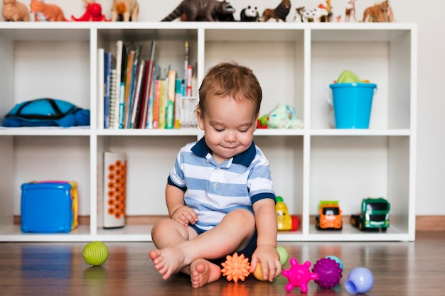 Front view of happy cute baby boy playing with toys