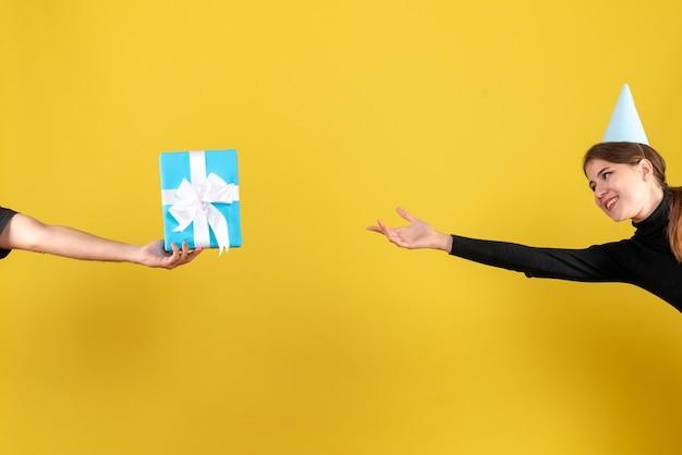 Вид спереди счастливая милая девушка с кепкой пытается достать подарочную коробку