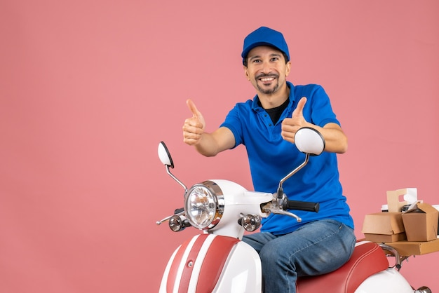 Front view of happy delivery guy wearing hat sitting on scooter making ok gesture on pastel peach background