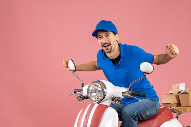 Front view of happy delivery guy wearing hat sitting on scooter on pastel peach background