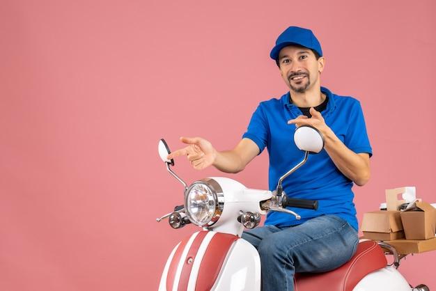 Vista frontale del ragazzo delle consegne felice che indossa un cappello seduto su uno scooter su sfondo color pesca pastello