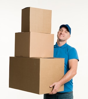 Front view of happy delivery man holding cardboard boxes