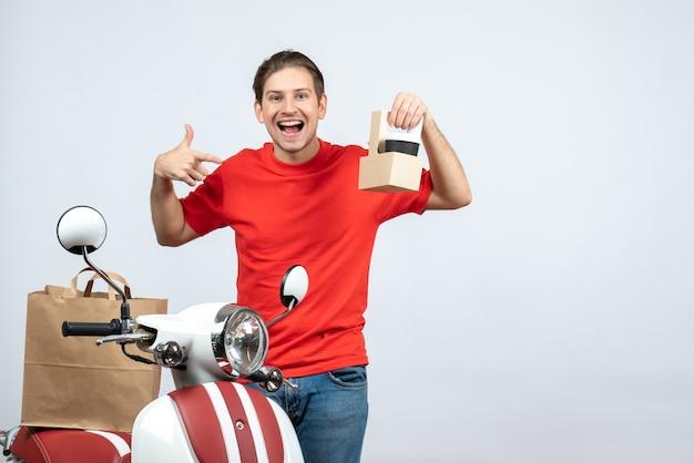 Vista frontale dell'uomo di consegna felice in uniforme rossa che sta vicino al motorino che mostra l'ordine su fondo bianco