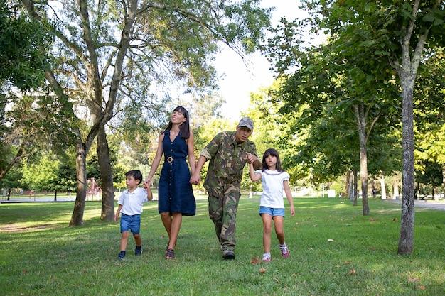 Vista frontale della famiglia felice che cammina insieme sul prato nel parco. padre che indossa l'uniforme militare e mostra qualcosa alla figlia. mamma dai capelli lunghi che sorride. ricongiungimento familiare e concetto di ritorno a casa