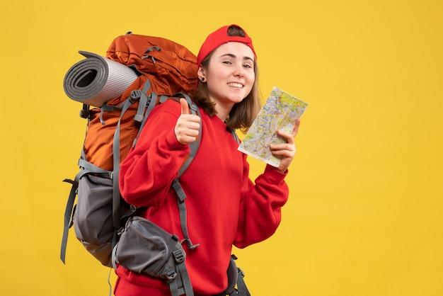親指をあきらめて旅行マップを保持している正面図幸せな女性のバックパッカー 無料写真
