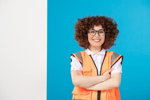 Vista frontale del costruttore femminile felice in uniforme sulla parete blu