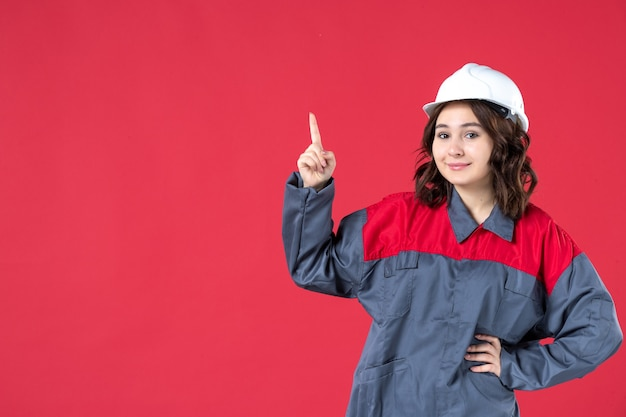 Front view of happy female builder in uniform with hard hat and pointing up on isolated red background