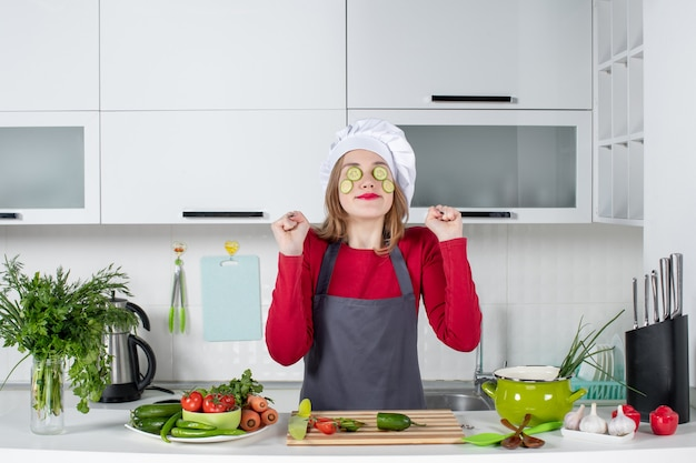 Front view happy female chef in uniform putting cucumber slices on her face