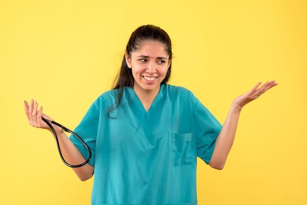 Вид спереди счастливая женщина-врач, держащая стетоскоп, открывая руки, стоя на желтом фоне